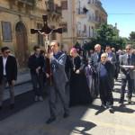 Il presidente dell'Ordine dei Medici regge il Crocifisso durante la processione