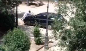 Un altro frame del video che mostra l'uomo mentre lava l'auto